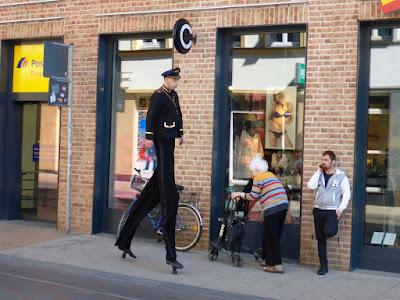 Mann mit Stelzen unter dem Anzug schreitet durch Schwerin