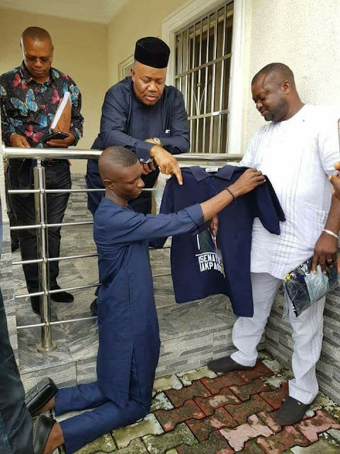 Trending photo of ex-Akwa Ibom state governor, Godswill Akpabio receiving a campaign shirt from an artisan who knelt down to present it