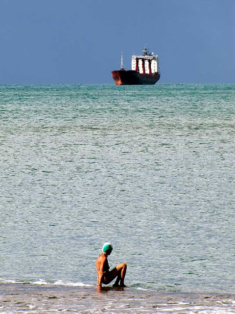 Bather at the edge of water, cargo ship at the horizon, Rotonda di Ardenza, Livorno