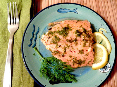 Reheated salmon served with lemon and dill garnish