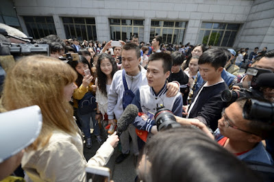 Sun Wenlin and his partner, Hu Mingliang, talk to journalists after losing their trial