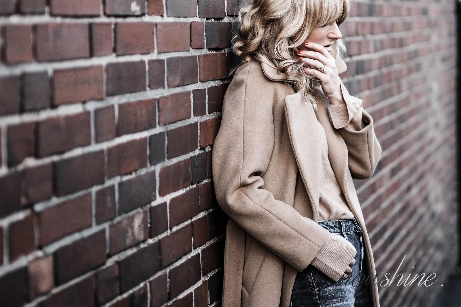 Nowshine trägt einen Mantel und Rollkragenpullover in Camel