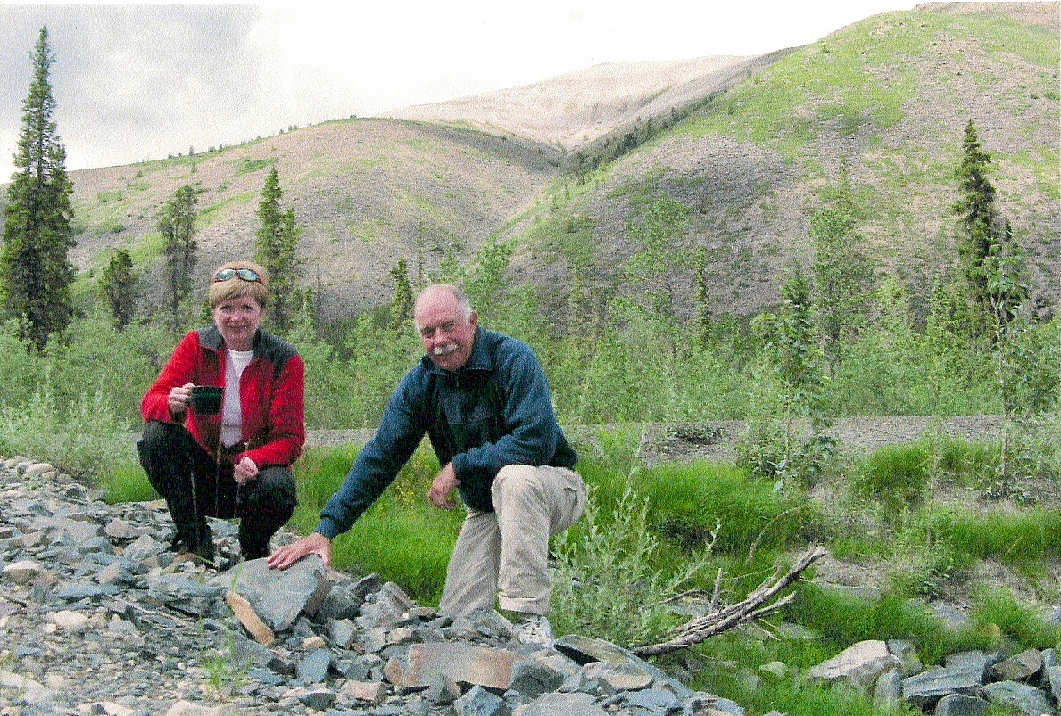 woman and man drinking tea in a remote area of Yukon, mountains behind