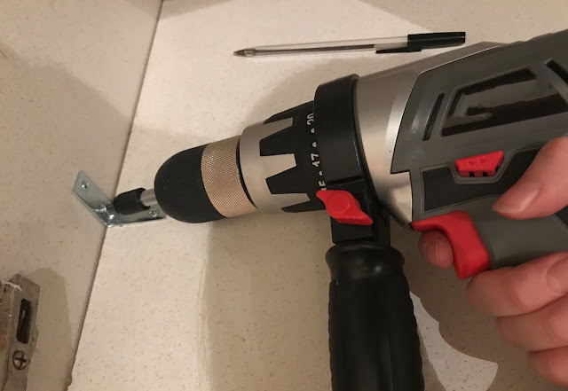 Close up of a hand using an electric drill to screw in a corner bracket