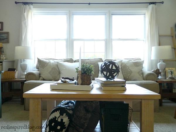 A cottage-like summer living room tour using whites, neutrals, and small pops of color in furniture and plants. beige sofa couch, wood coffee table, alabaster white walls, beige carpet, pillows, plant, books,driftwood, metal orb sphere ball, white curtains.