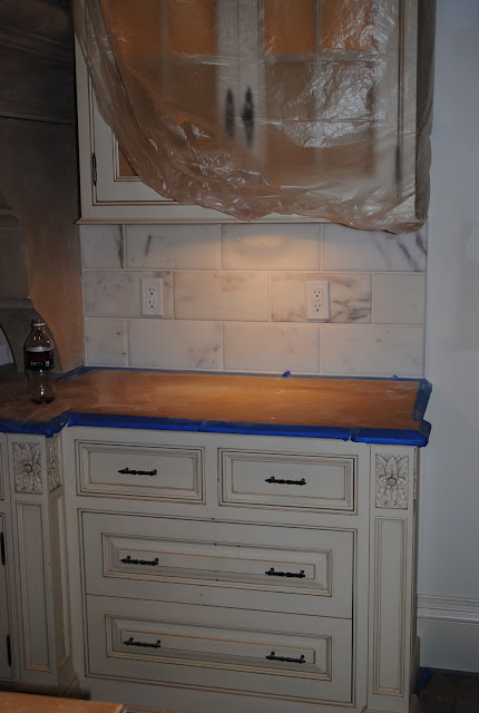 Detail of under construction Enchanted Home kitchen by Tina with large marble subway backsplash