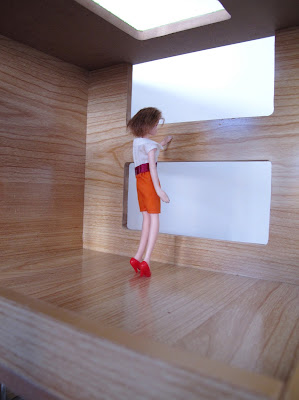 A doll looking through the mezzanine windows of the modern Lori Loft to Love dolls' house.