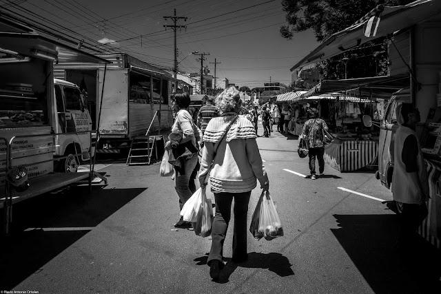 Senhora com sacolas na feira