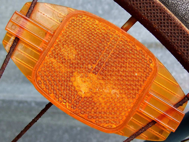 Large photo of an orange bicycle reflector