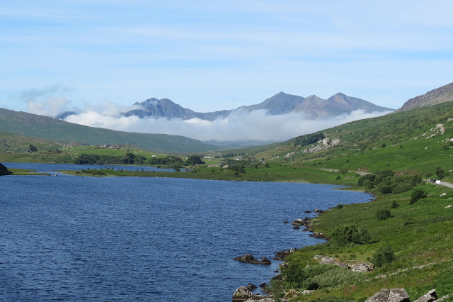 A lake and hills - at the end of the valley is Snowdon, its highest peaks rising out of a band of cloud.