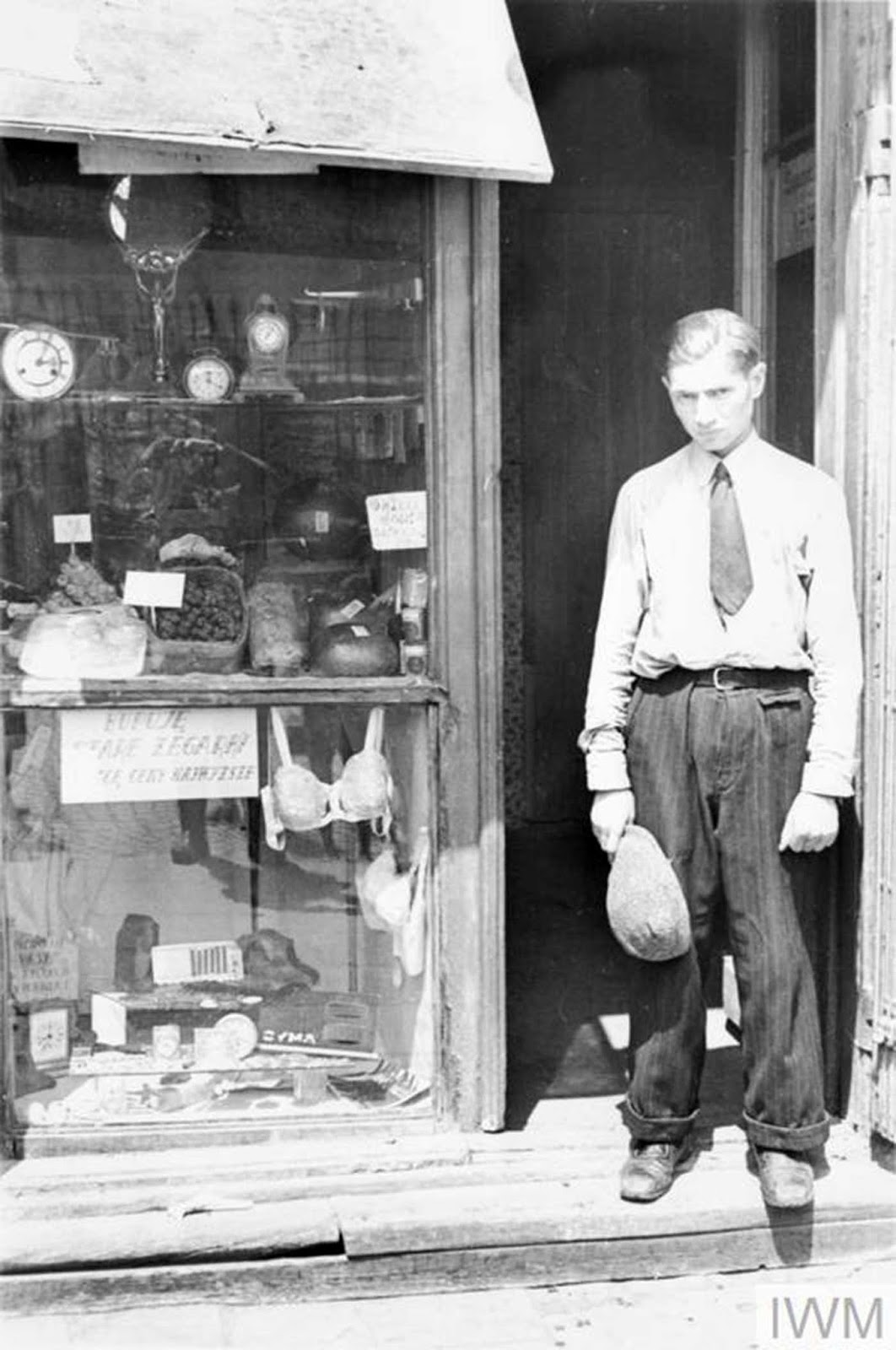 A young man in the doorway of a shop in the ghetto. Note he has taken his hat off to comply with the German order to remove headwear in the presence of German personnel. The shop offers fresh eggs, sweets and watches. The sign in the window reads -