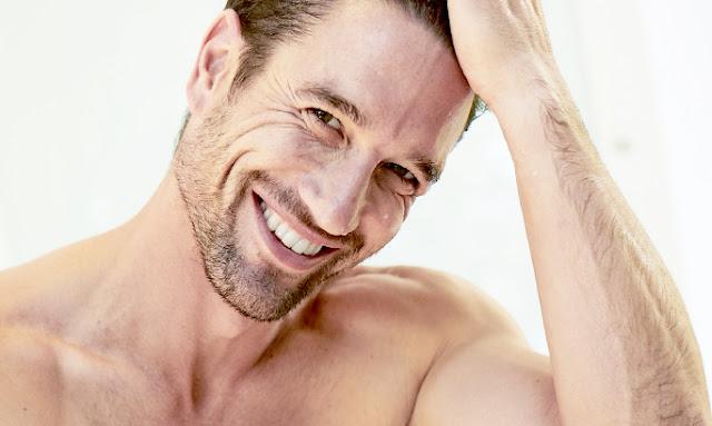 Λευκός άνδρας ημιγυμνος χαμογελά και πιάνει τα μαλλιά του - Συμβουλή ειδικού Aπαντάμε τις πιο συχνές ερωτήσεις για την ανδρική περιποίηση