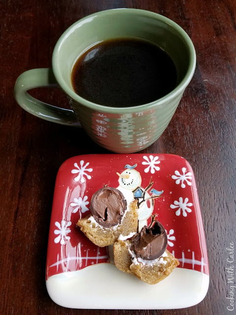 snowman plate with a s'mores cookie cup split in half and a cup of coffee nearby