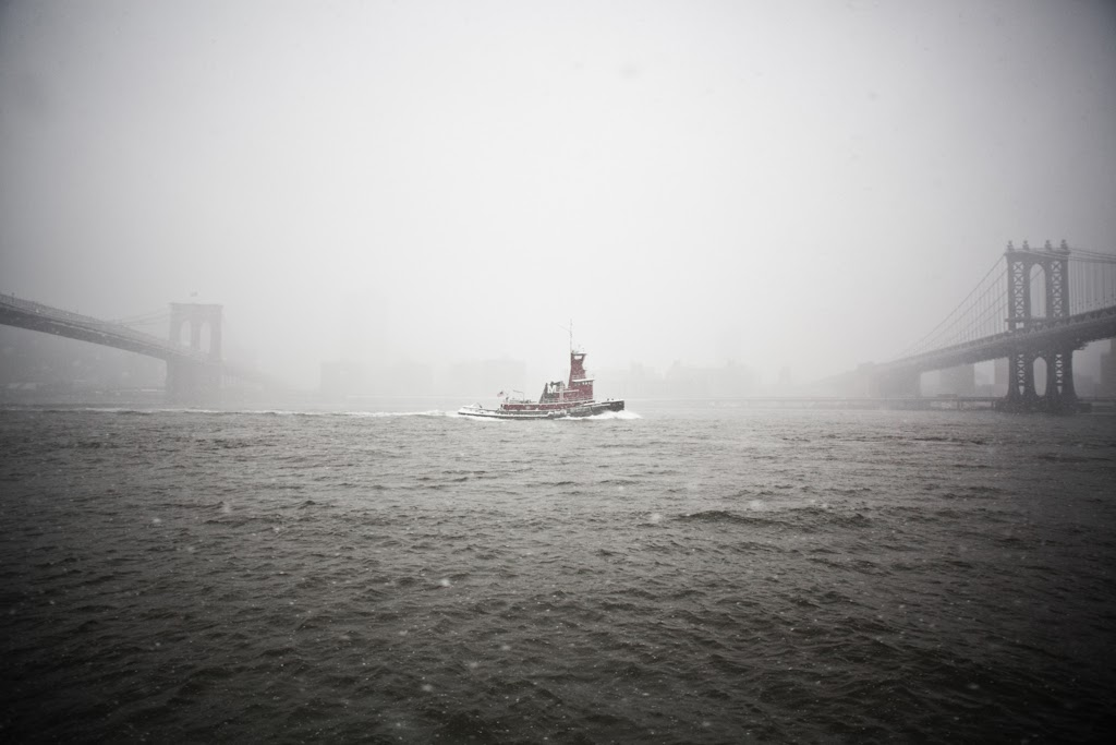 A tugboat passes between the Brooklyn and Manhattan Bridge, Dumbo, New York