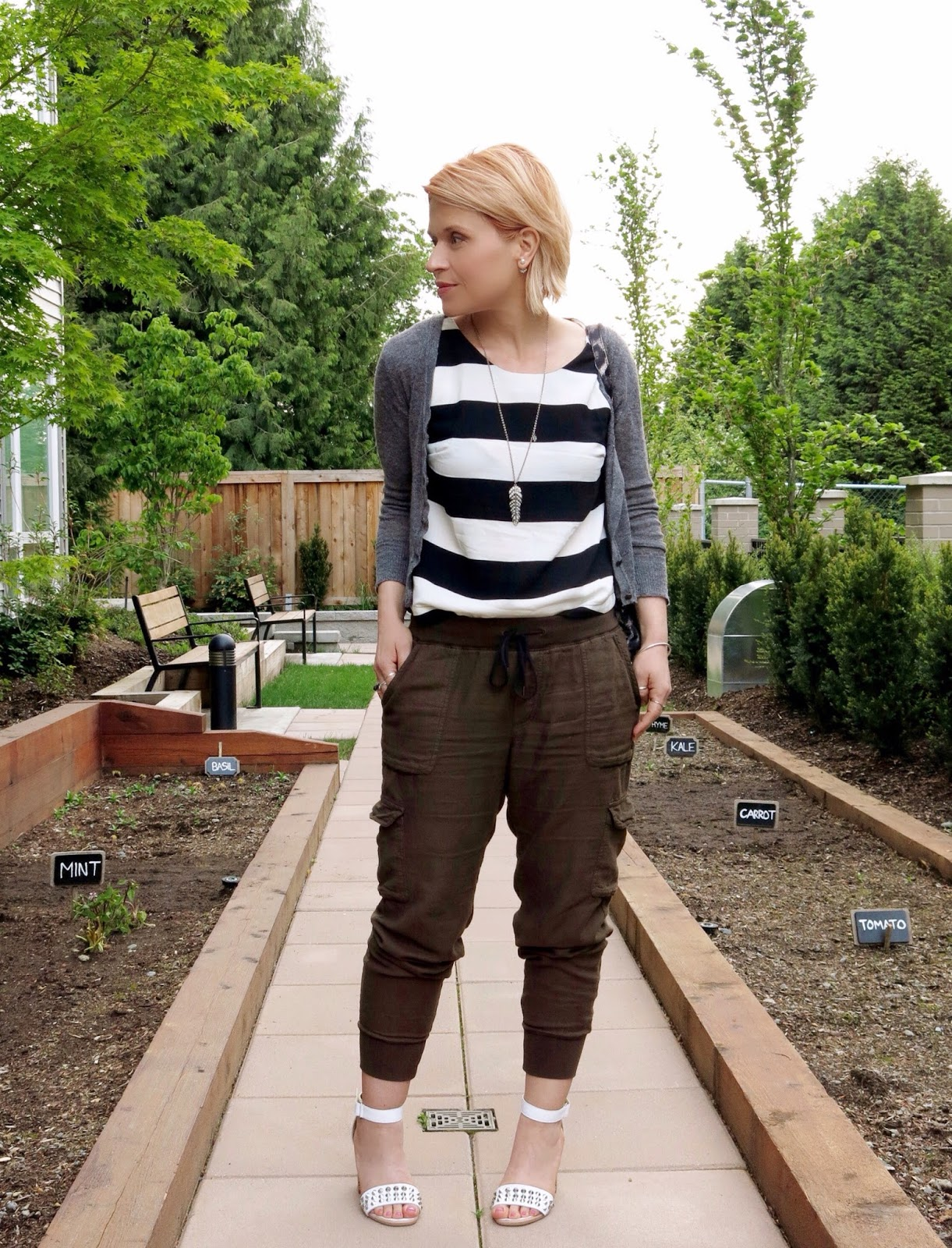 styling slouchy cargo pants with a striped tank top, shrunken cardigan, and studded ankle-strap sandals