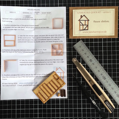 Pieces of a one-twelfth scale house shelves kit and instruction sheet, arranged on a cutting board with a ruler, cutting knife and tweezers.