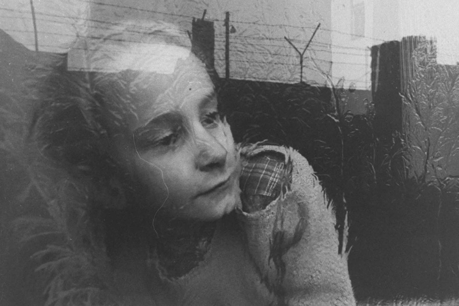 A young girl gazes pensively through the pane of her apartment window, which reflects the image of barbed wire fencing that tops the nearby Berlin Wall, in December 1962.