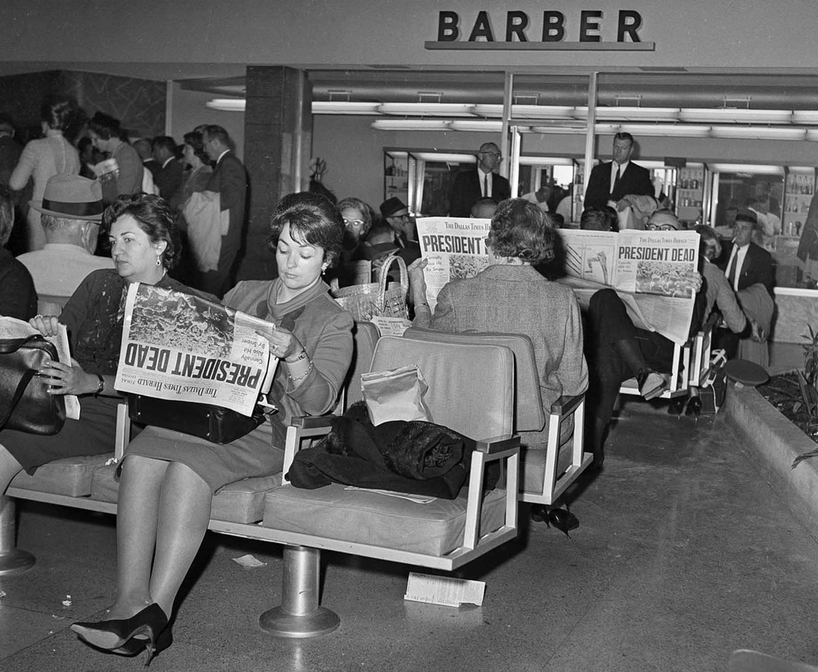 People waiting for flights from Dallas at Love Field read the news of President John F. Kennedy's assassination in the Dallas Times Herald newspaper, on November 23, 1963.