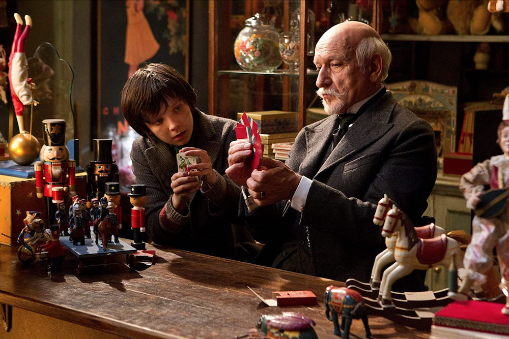 Asa Butterfield as Hugo Cabret and Ben Kingsley as Georges Méliès at counter in toy shop adorned with nutcracker soldiers, miniature rocking horses, and other hand-crafted figurines