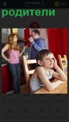 за столом сидит ребенок, а сзади стоят его родители и разговаривают