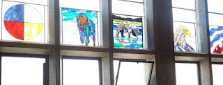 stained glass windows at the chapel, all saints cathedral, edmonton. photo by rob goetze. windows, from left to right: medicine wheel, buffalo, bear, eagle