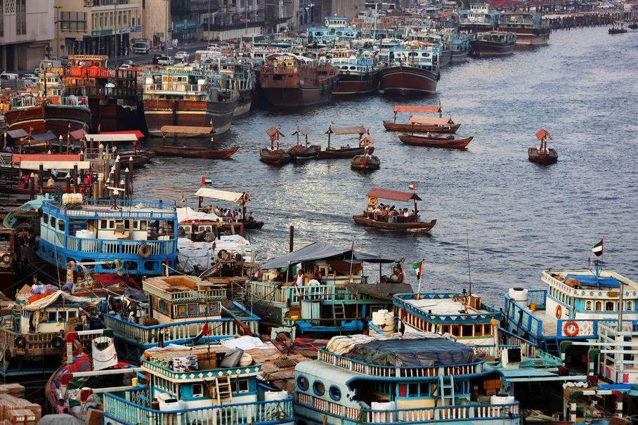 In this Monday, May 26, 2014 photo, trading dhows for uploading goods are docked at the creek in Dubai, United Arab Emirates. Beneath a glitzy skyline wooden boats ply Dubai Creek, the historic heart of a city that was transformed in little more than a generation from a tiny pearling and fishing port to a global trading hub.