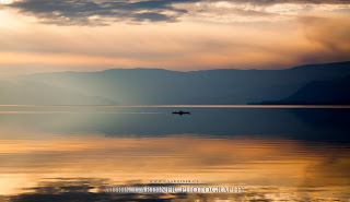 A lone kayaker on the glassy reflections of Lake Okanagan in the late fall, by Chris Gardiner Photography www.cgardiner.ca