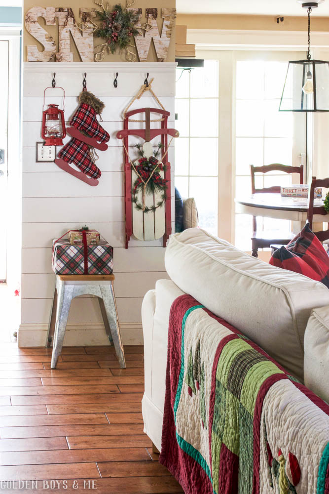 Let It Snow themed planked entryway wall with wooden sleigh