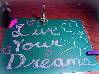 Chalk pastel on dark green paper: Live your dreams.  Two pieces of chalk pastel near the corners of the green paper.  A small Eiffle Tower figure near top of green page and a cat tail peaking in the corner of the image.
