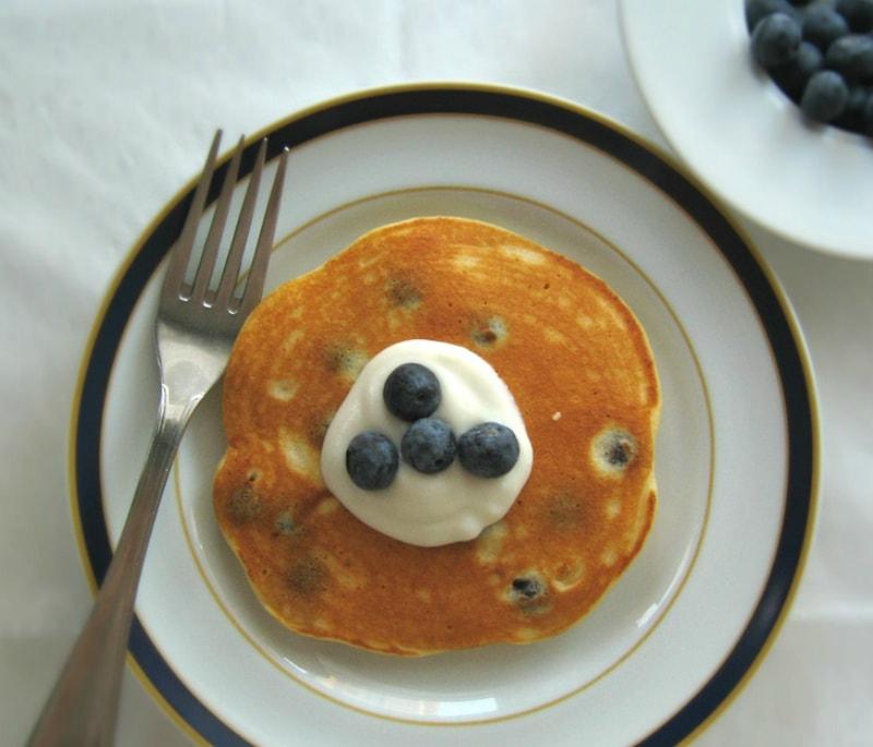 Panquecas de mirtilos e ricotta no prato cobertas de quark e mirtilos frescos / Blueberry & ricotta pancakes on a plate covered with quark and fresh blueberries
