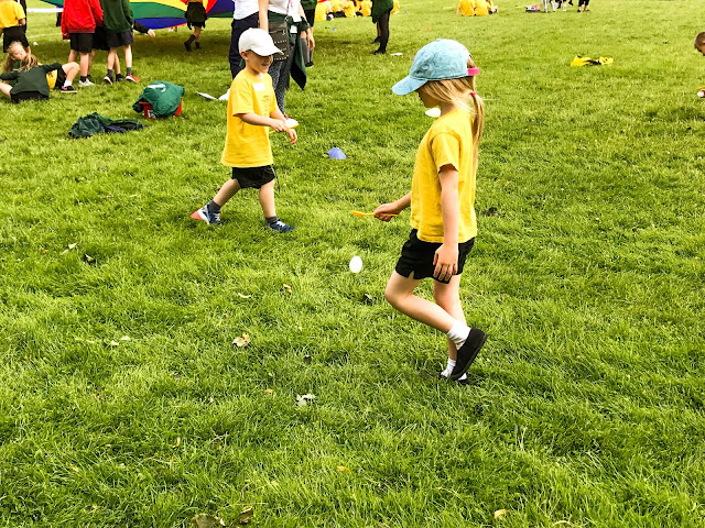 A young girl in yellow t-shirt, black shorts and blue hat is walking with good posture in the egg and spoon race. The egg has just fallen off the spoon.