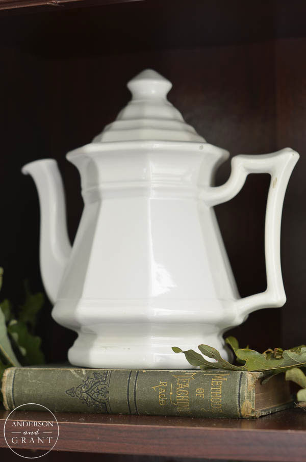 White pottery teapot displayed on a vintage book.  |  anderson + grant