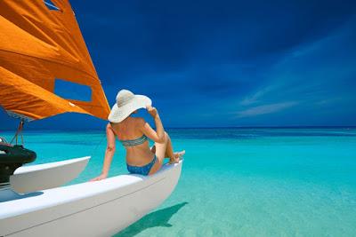Femme en bikini et chapeau à l'avant d'un catamaran fait face à la mer des Caraibes.