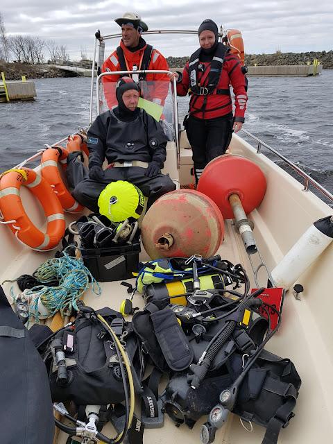 Vene täynnä sukellustarvikkeita ja kyydissä matkailuyrittäjä ja kaksi työkaveria.