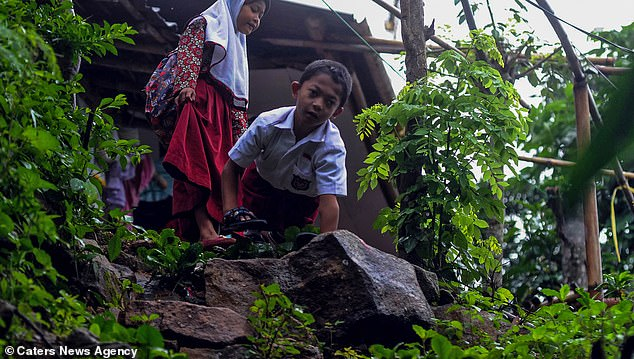 Eight-year-old Adul's daily walk to school takes him through the Indonesian forest and up steep slops.