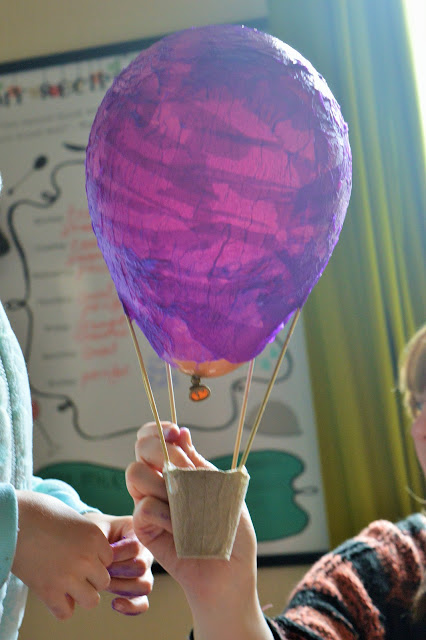 A ballon with finished layer of paper mache in purple.