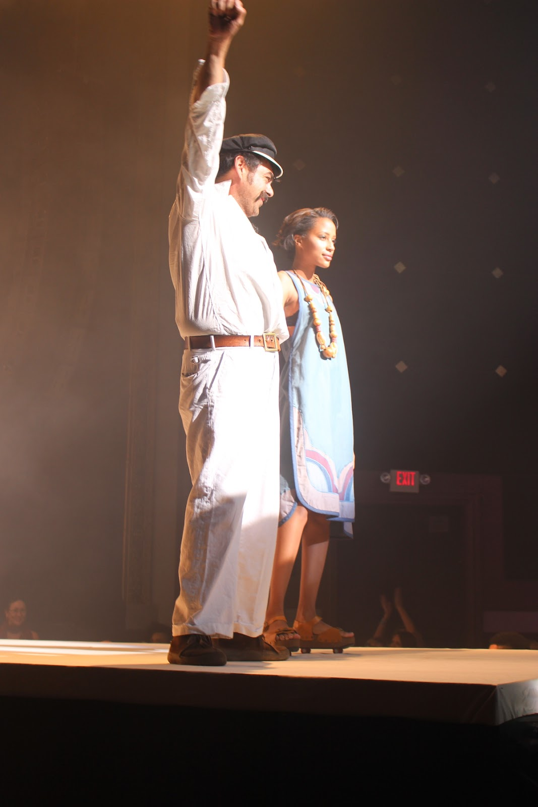 In this photo, Esteban has his arm raised thanking the audience for their applause. He is holding the hand of the model wearing his favorite piece in the collection.