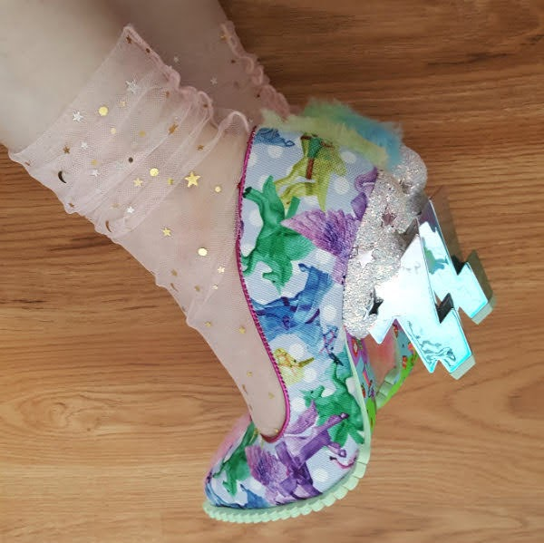 feet on floor wearing unicorn print pointed toe court shoe with cloud and lightning bolt heel