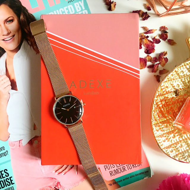 flatlay - cosmo magazine to the left side, red Adexe box in the centre, watch draped over it. Pineapple dish to the right with an essie polish on top, flowers in the right hand corner