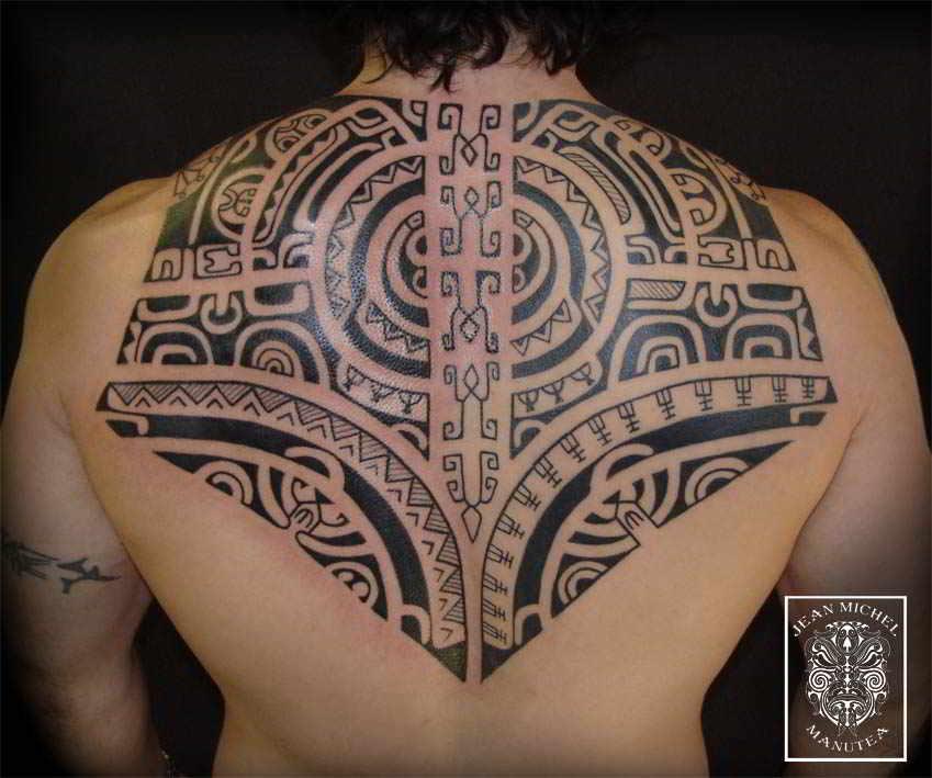 un hombre con tatuaje maori en la espalda