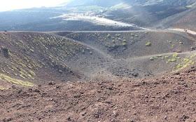 uno dei crateri silvestri e sullo sfondo il rifugio sapienza e il parcheggio