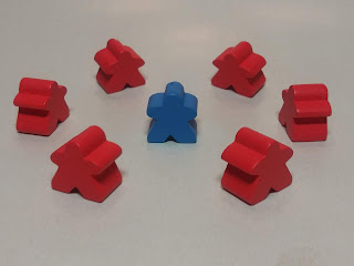 a circle of six red meeples surrounding a blue meeple, to symbolise the divisive nature of some people