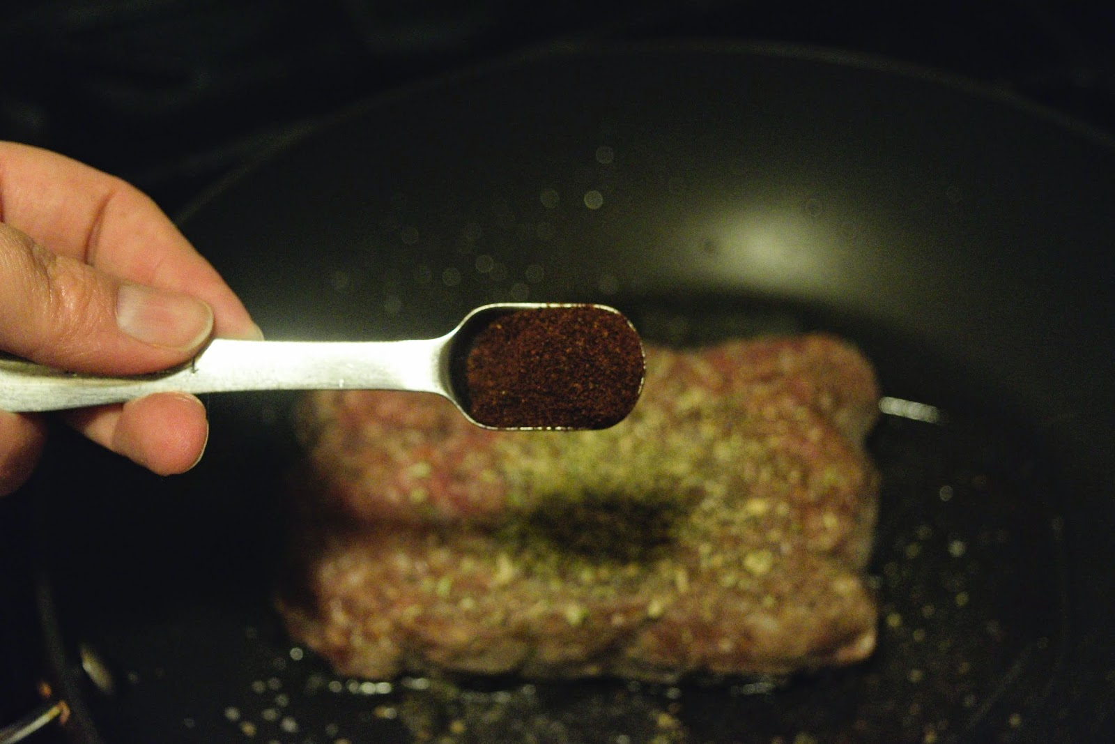 Chili powder being added to the ground beef in the pan.
