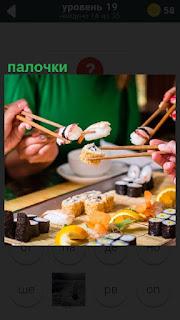 За столом принимают пищу палочками, очень похоже на суши