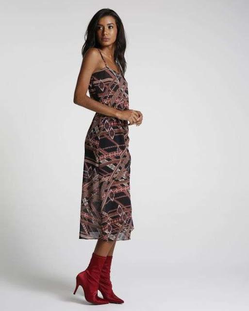 A peça possui modelagem midi, alças finas cruzada nas costas, elástico cinturando a peça, fenda e padronagem étnica. Possui forro.