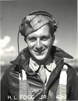 """A portrait of Howard Fogg in his WWII aviator flight gear with """"J. L. Fogg Jr. 42J"""" printed across the bottom in white lettering."""