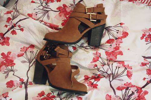 tan cut out ankle boots with slight heels and two gold buckles on overlapping straps on the side, sitting next to each other on a red and pink floral bedspread