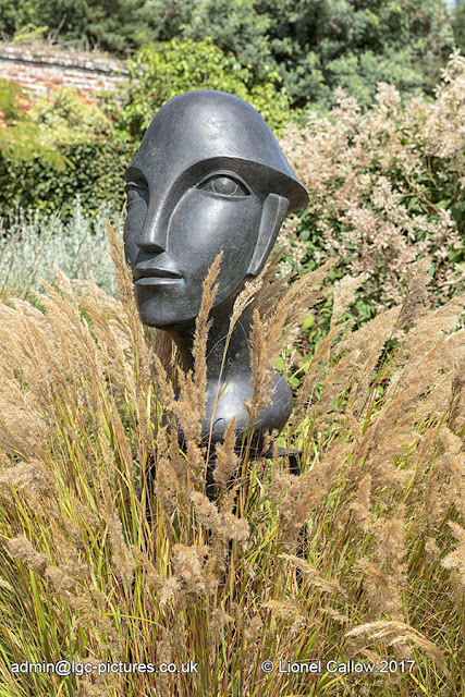 This is a sculpture set in a flower bed of ferns, with a African theme made with bronze resin