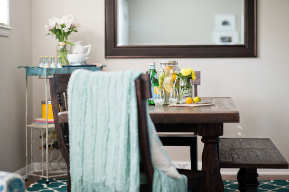 This decorated turquoise bar cart adds character to the dining room.