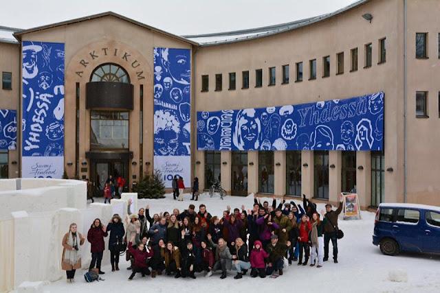 Arktikum-museo, jonka edessä seisoo joukko ihmisiä poseeraamassa kameralle